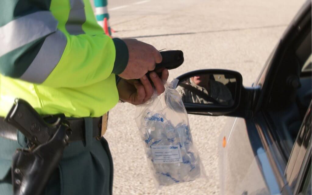 imagen de un control de alcoholemia en el que un Guardia Civil sostiene las boquillas con las que se toman las mediciones de alcohol en sangre.