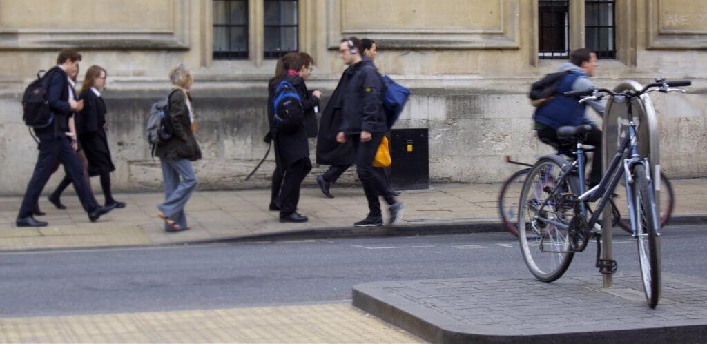 Imagen de una bicicleta aparcada en la calle con transeúntes por detrás.
