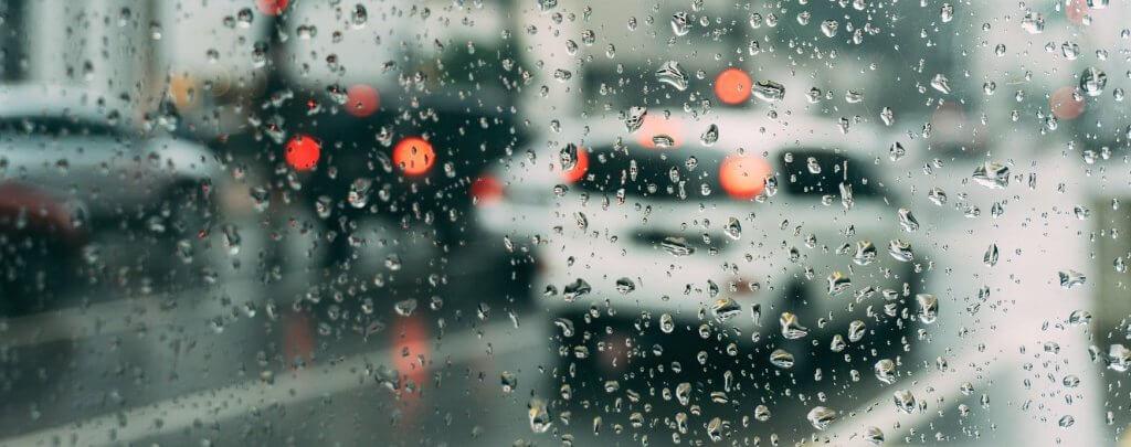 Carretera mojada, circulación con lluvia en la ciudad.