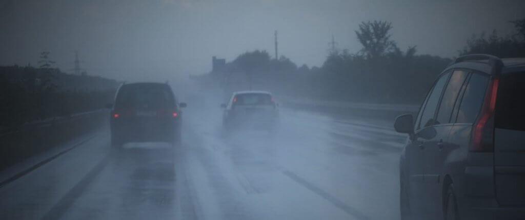 Carretera con lluvia y coches circulando en condiciones atmosféricas adversas.